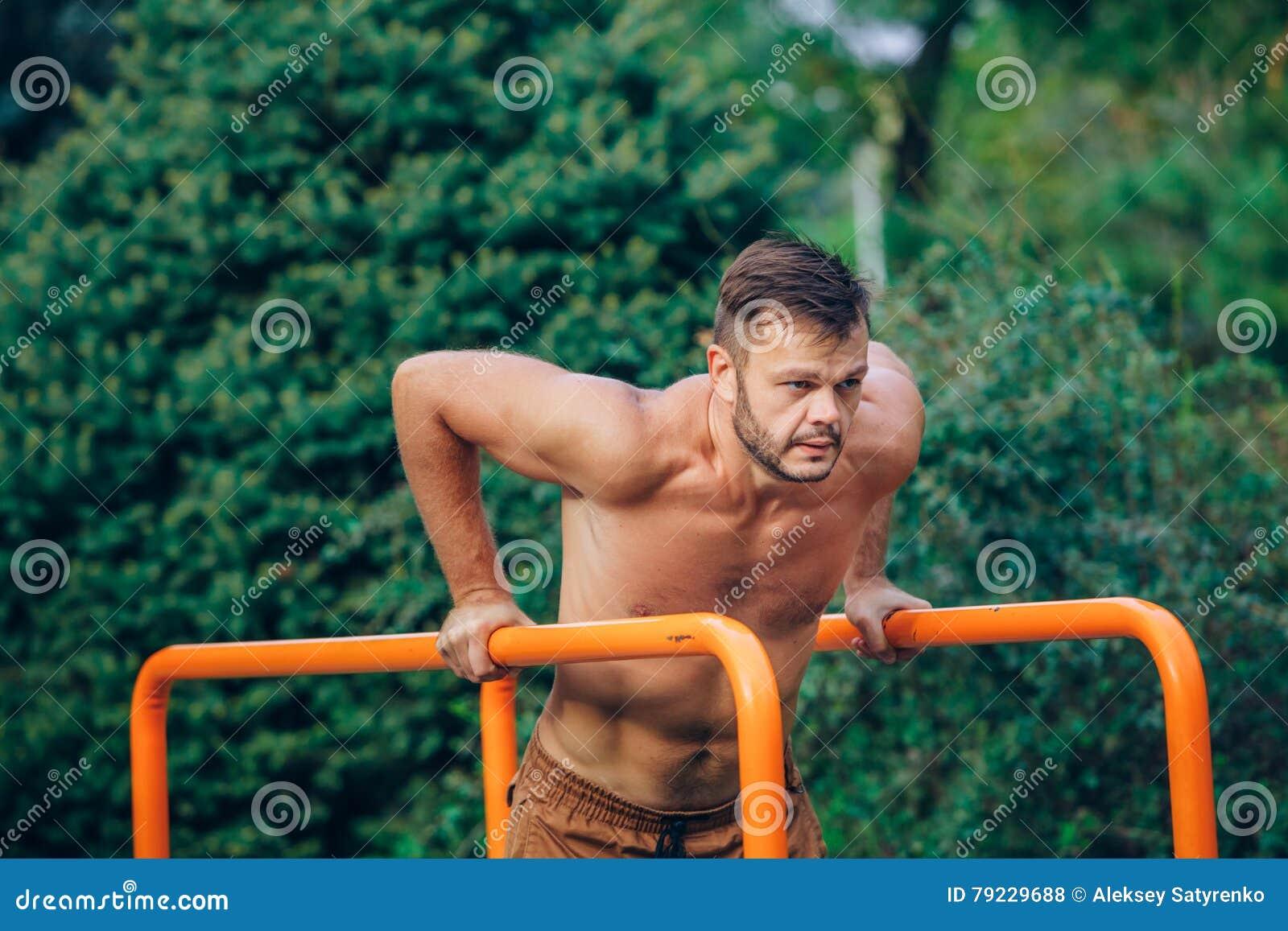 Eignung, Sport, trainierend, Ausbildungs- und Lebensstilkonzept - der junge Mann, der Trizeps tut, tauchen auf Barren draußen ein