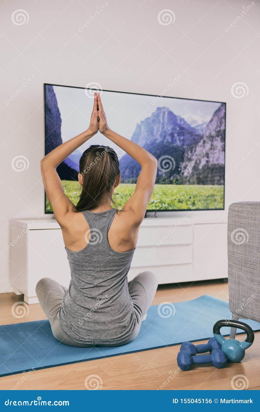 Eignungsklasse des Yoga zu Hause, die im Fernsehen Appon-line-Frauentraining im Wohnzimmer auf der Übungsmatte allein meditiert -