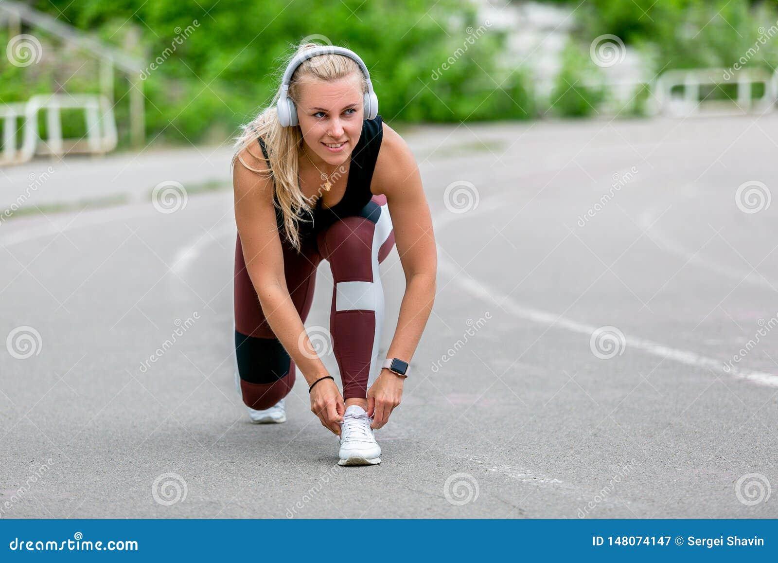 Eignungslebensstil Junge Frau in den Kopfhörern, welche die Spitzee bevor dem Rütteln binden Training am Stadion Gesundes Lebenko
