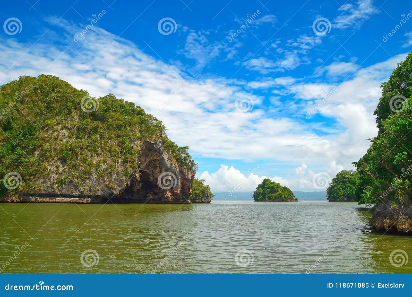 Eiland, rots in de Atlantische Oceaan met groene vegetatie, tegen een achtergrond van de kust op de achtergrond wordt behandeld d