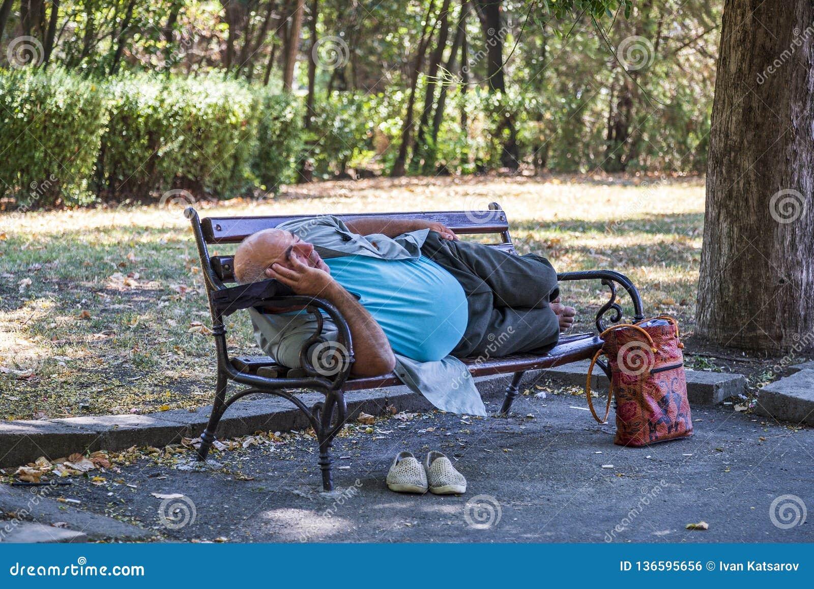 Ein älterer Mann, der barfuß auf einer Bank im Stadtpark liegt und mitten in dem Tag in Burgas/Bulgaria/08/14/2016 schläft