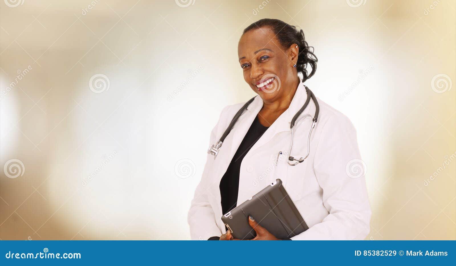 Ein älterer schwarzer Doktor, der für ein Porträt in ihrem Büro aufwirft