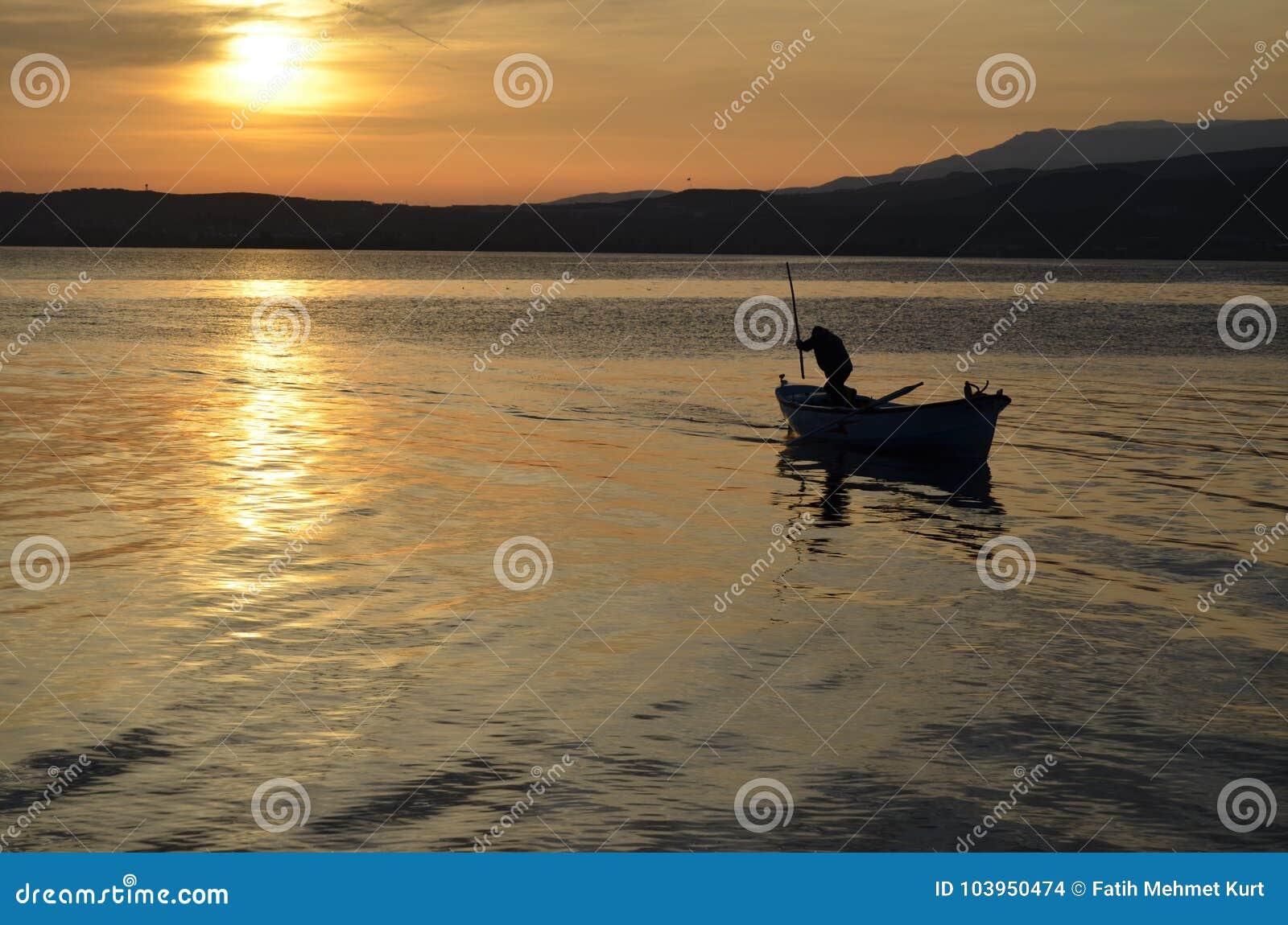 Ein alter Fischer auf dem See bei Sonnenaufgang