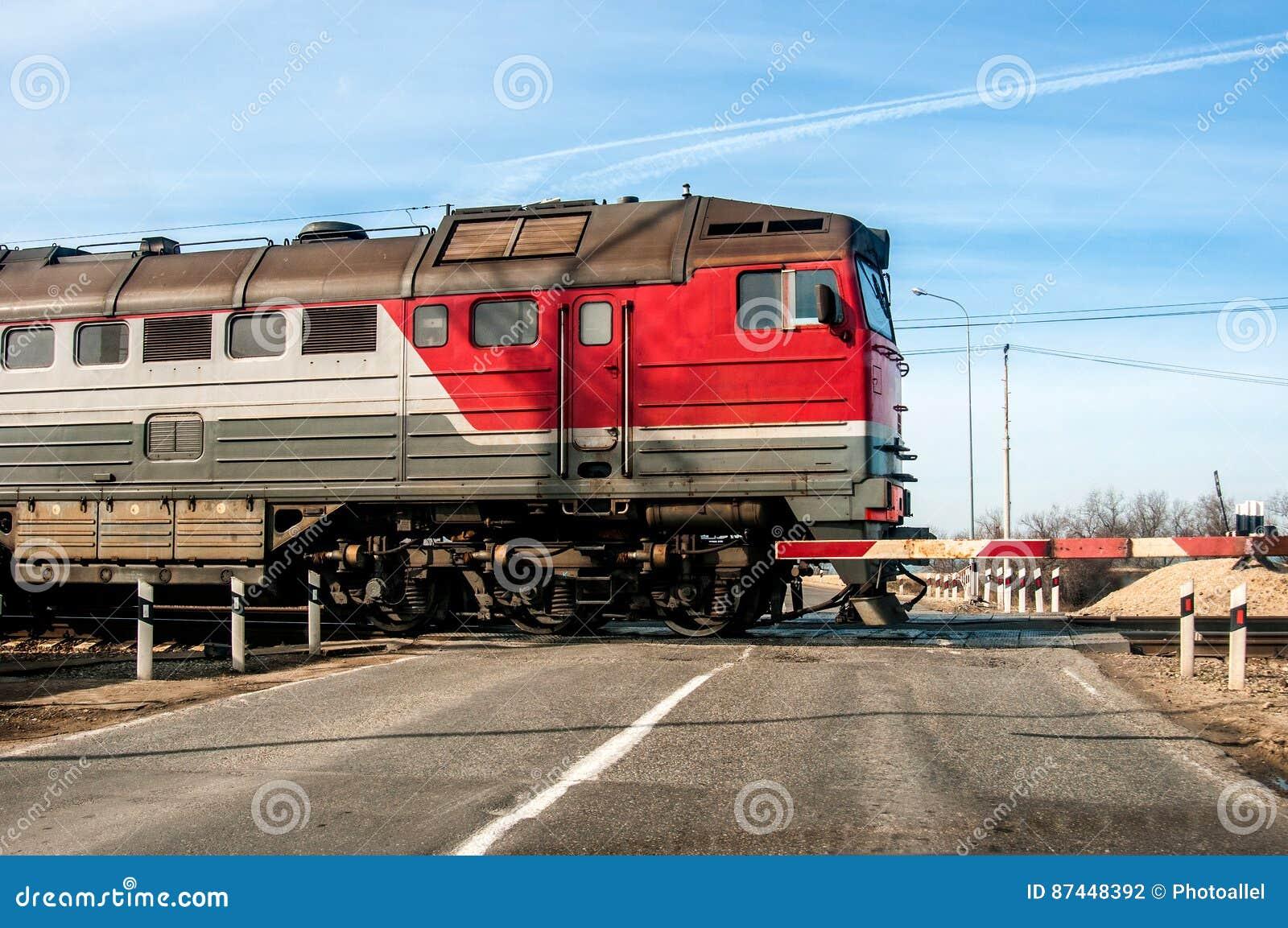 Ein alter russischer roter Zug, der über einen Niveauübergang, auf einer kleinen Straße überschreitet