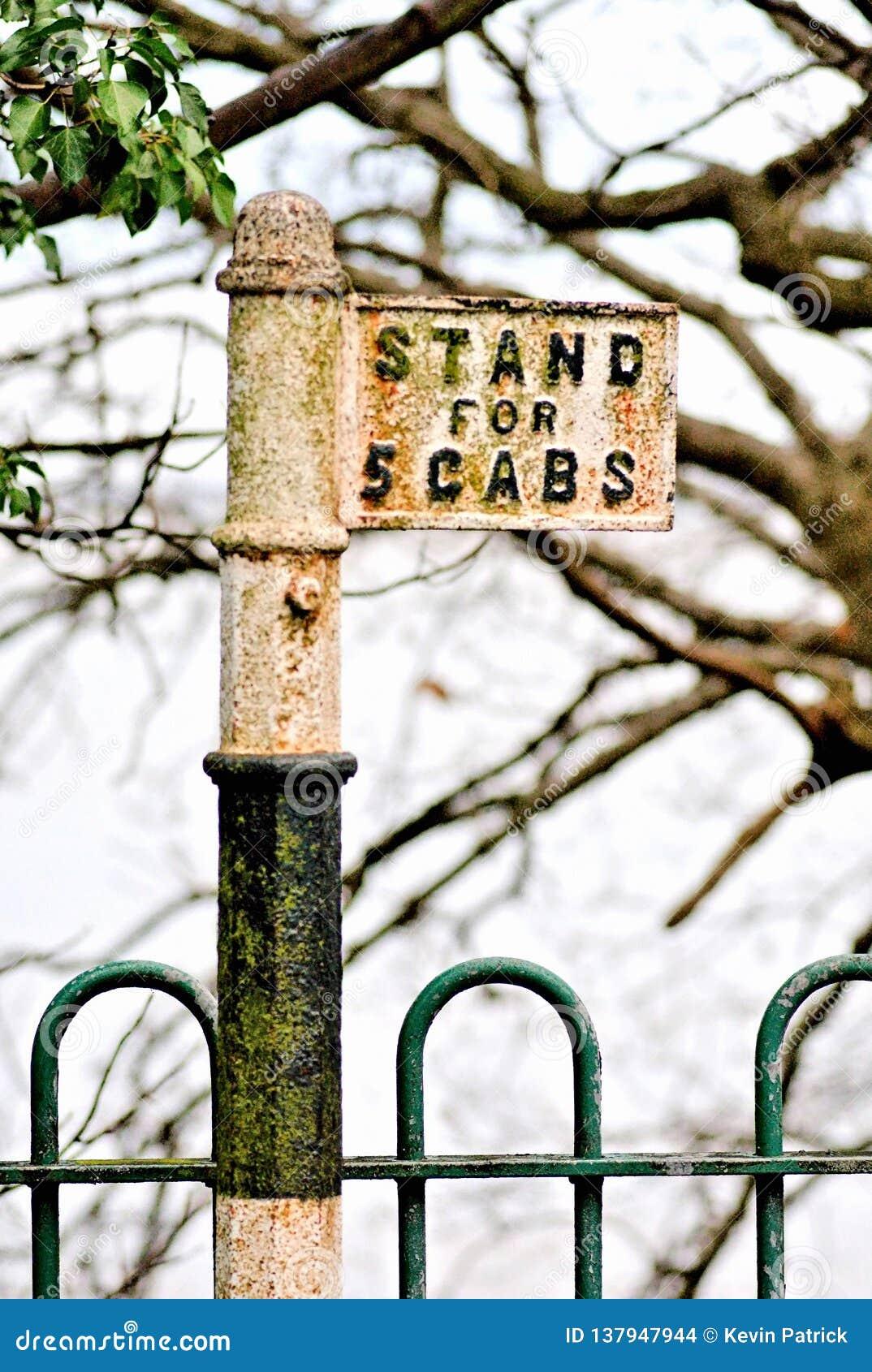 Ein altes britisches ein einziger Fahrerhaus-Stand lokalisiert und beim durch Wald-und Schmiedeeisen-Fechten gesäumt Zeichen von