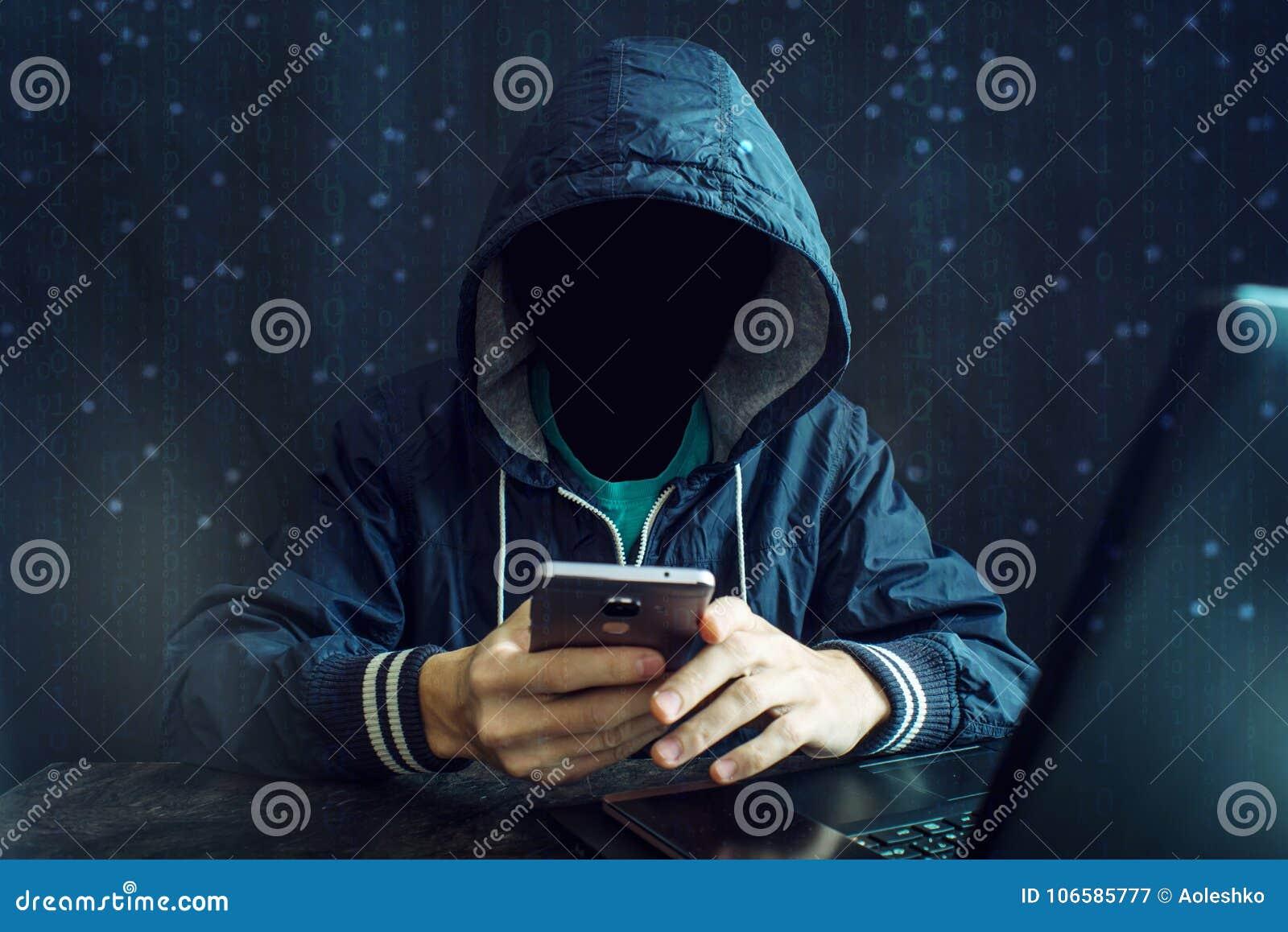 Ein anonymer Hacker ohne ein Gesicht benutzt einen Handy, um das System zu zerhacken Das Konzept des Cyberverbrechens