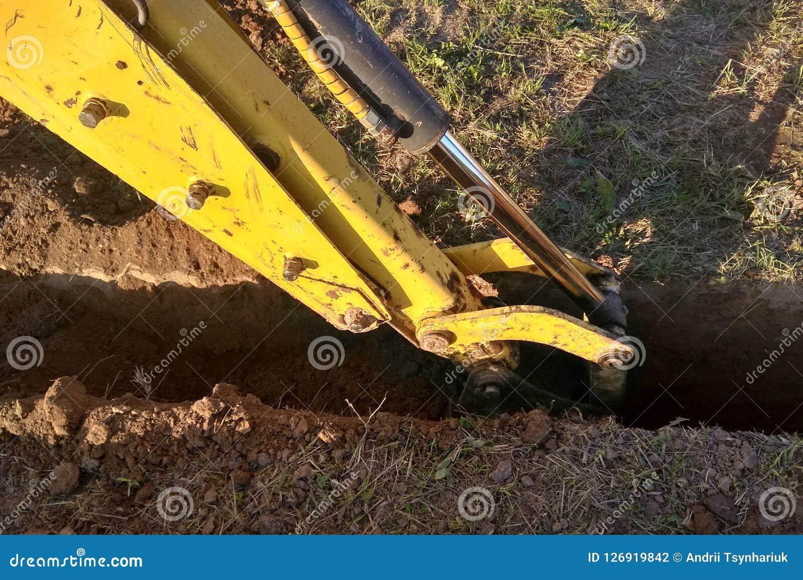 Ein Arbeitsbagger, der einen Graben für die Grundlage eines Gebäudes gräbt