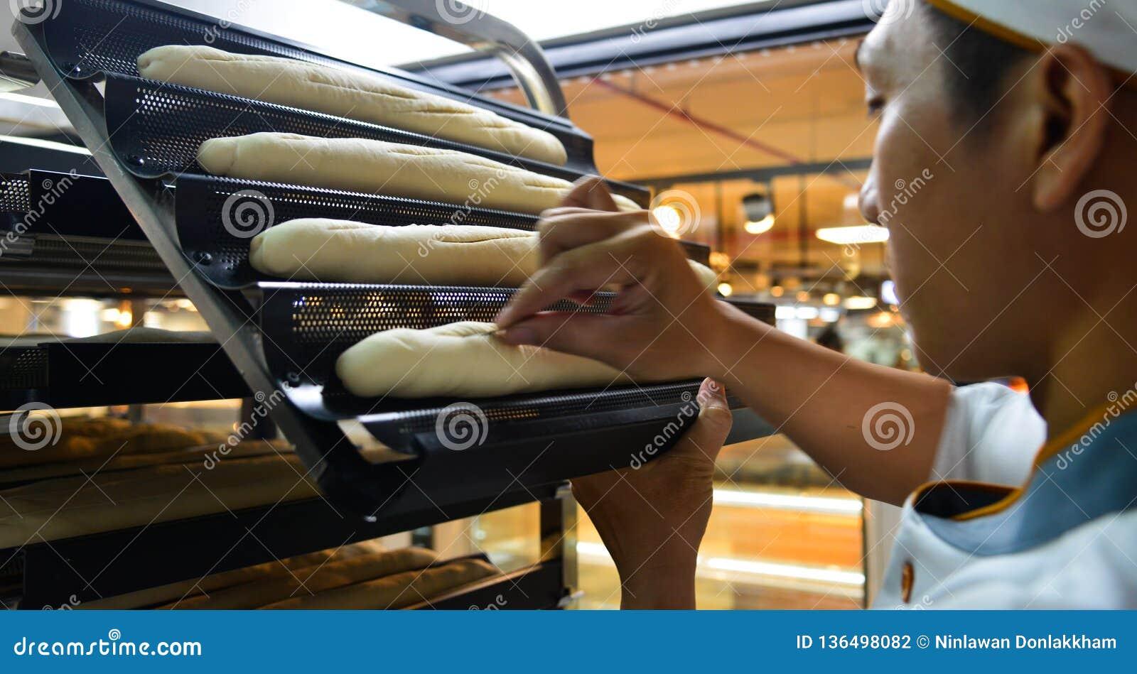 Ein asiatischer Mann, der Brot an der Bäckerei macht