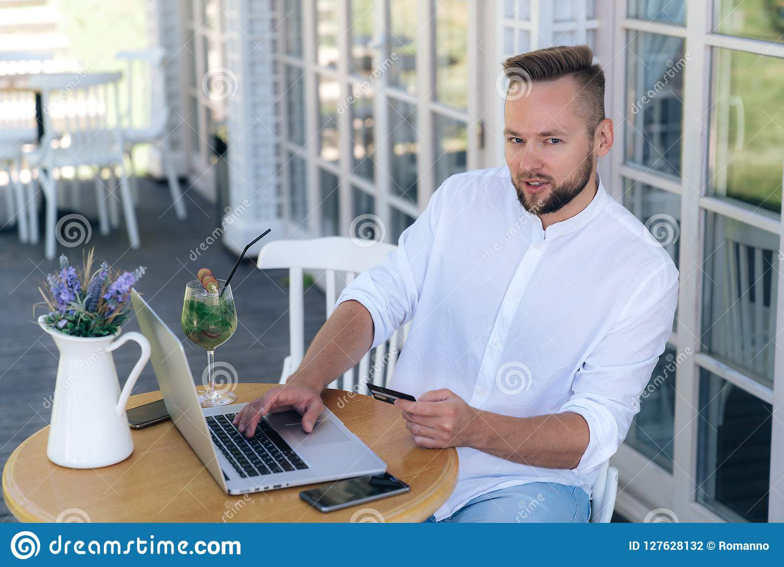 Ein attraktiver stilvoller junger Mann arbeitet in einem Café, leistet Zahlungen von einer Bankkarte im Internet, verwendet einen