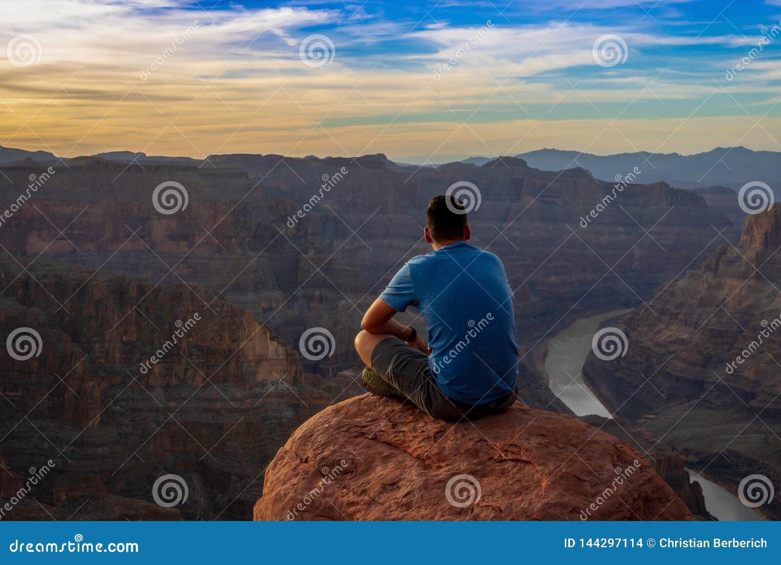 Ein aufpassender Sonnenuntergang des Mannes bei Grand Canyon