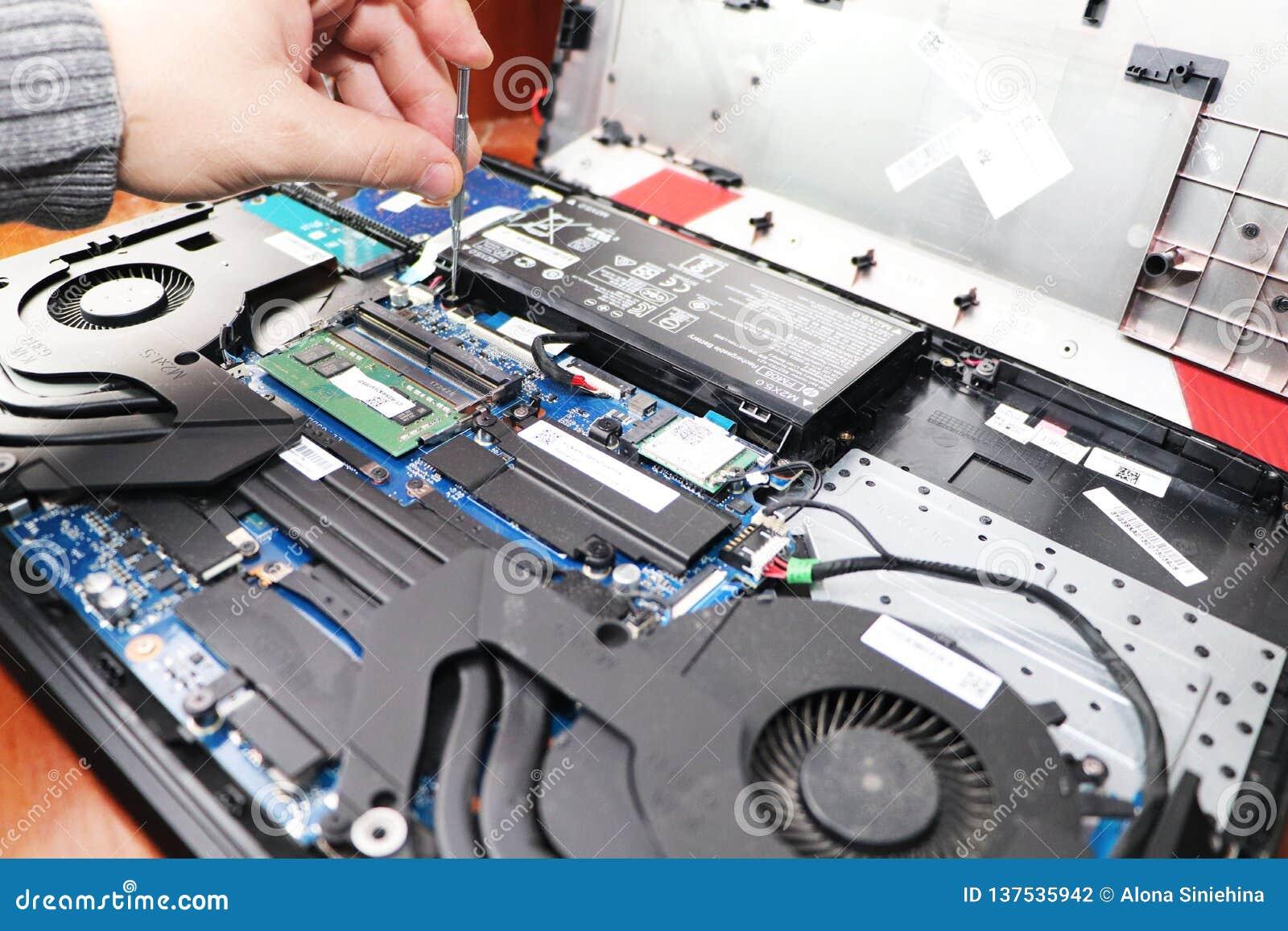 Ein Aussenseiter säubert eine Laptopkühlvorrichtung Verseuchtes Kühlsystem des Computers