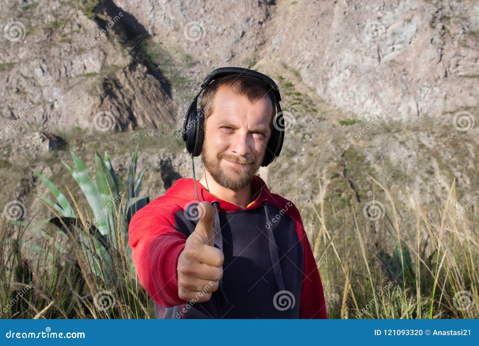 Ein bärtiger Mann hört Musik auf Kopfhörern, in der Natur Es gibt Berge hinter es Er zeigt sich seinen Daumen