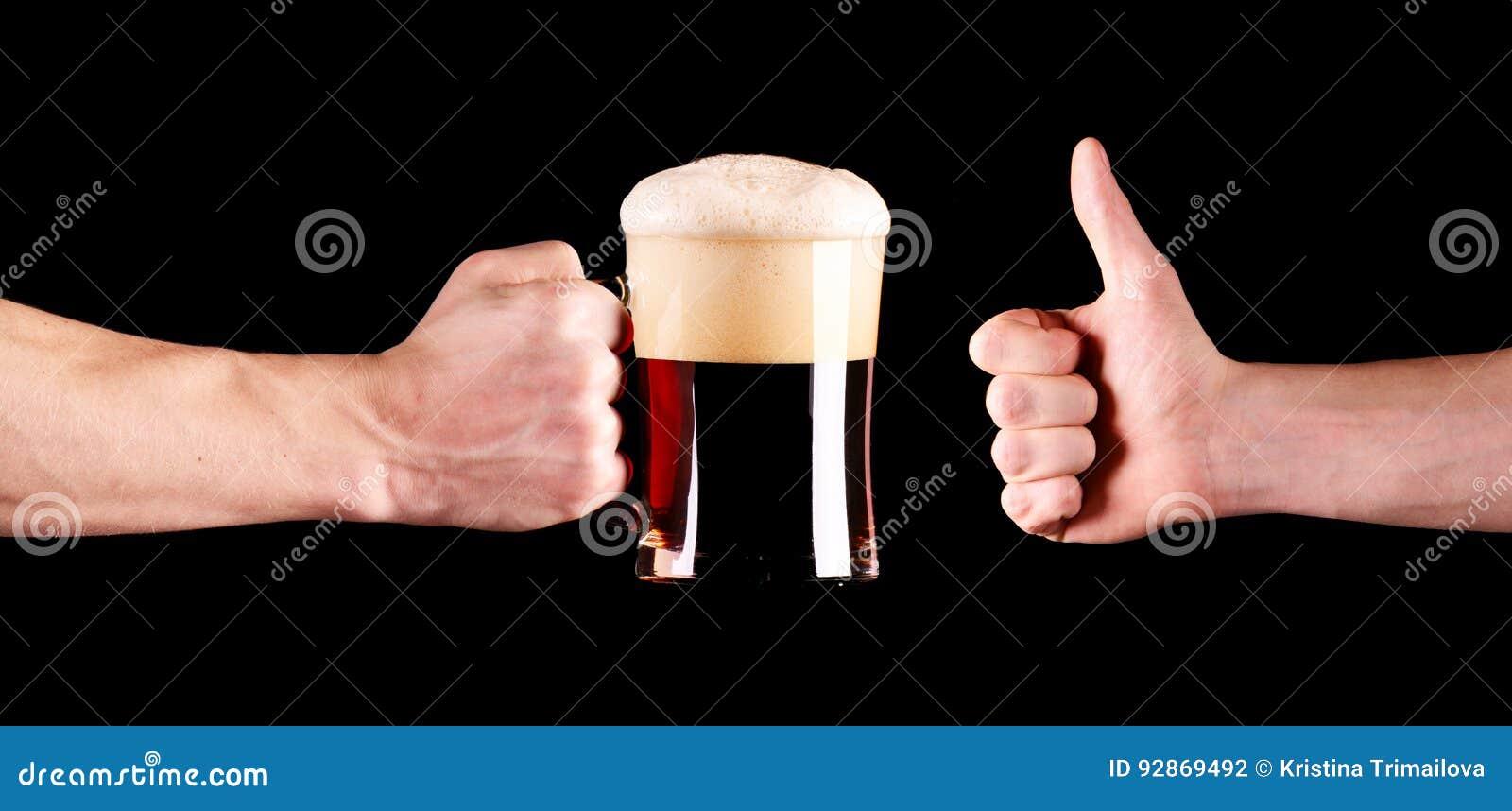 Ein Becher schwarzes Bier in der Kerlhand Daumen herauf die Hand lokalisiert auf schwarzem Hintergrund