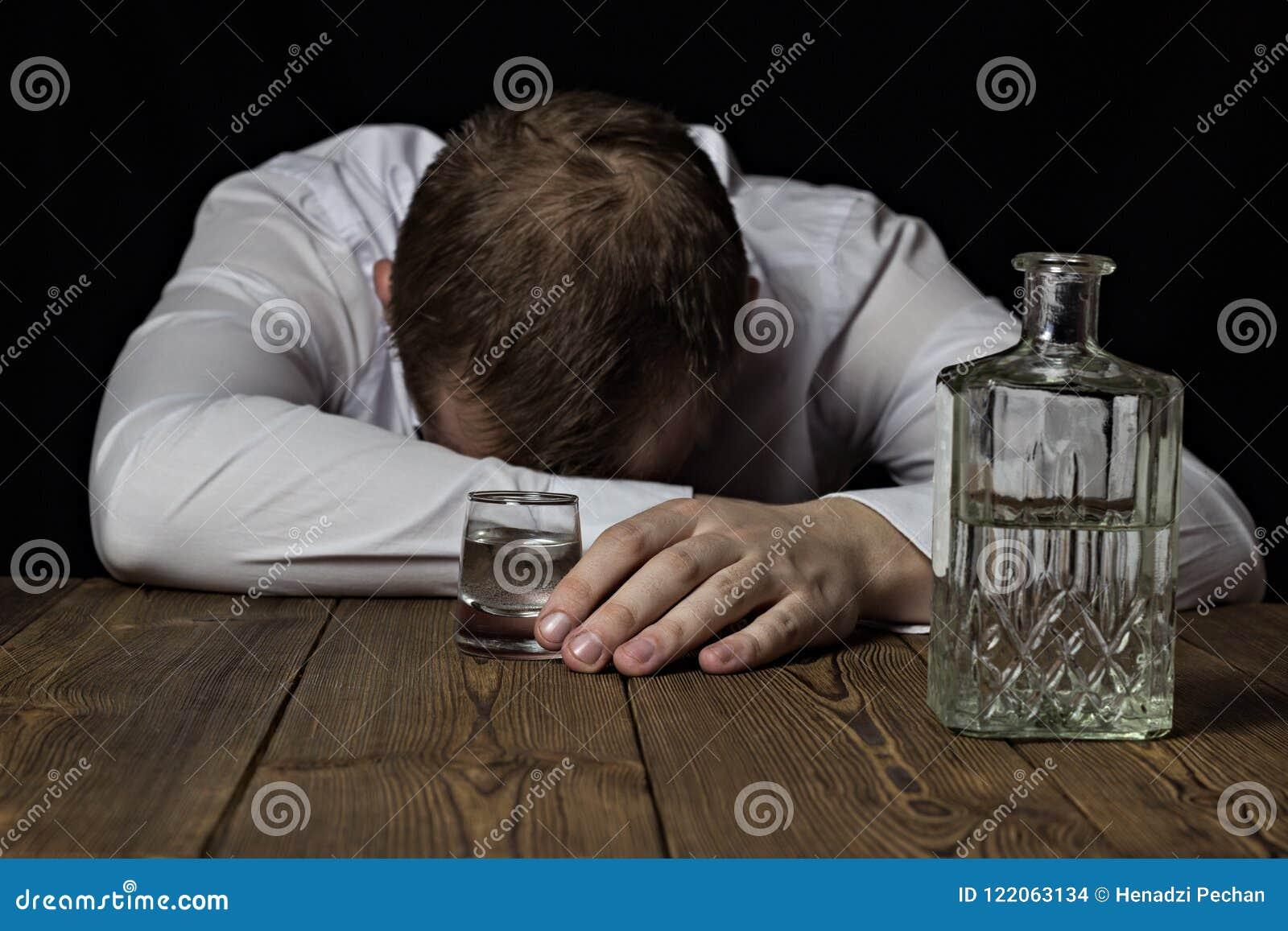 Ein betrunkener Geschäftsmann liegt auf einer Tabelle, in seiner Hand ein Schuss des Weins mit Alkohol, ein schwarzer Hintergrund