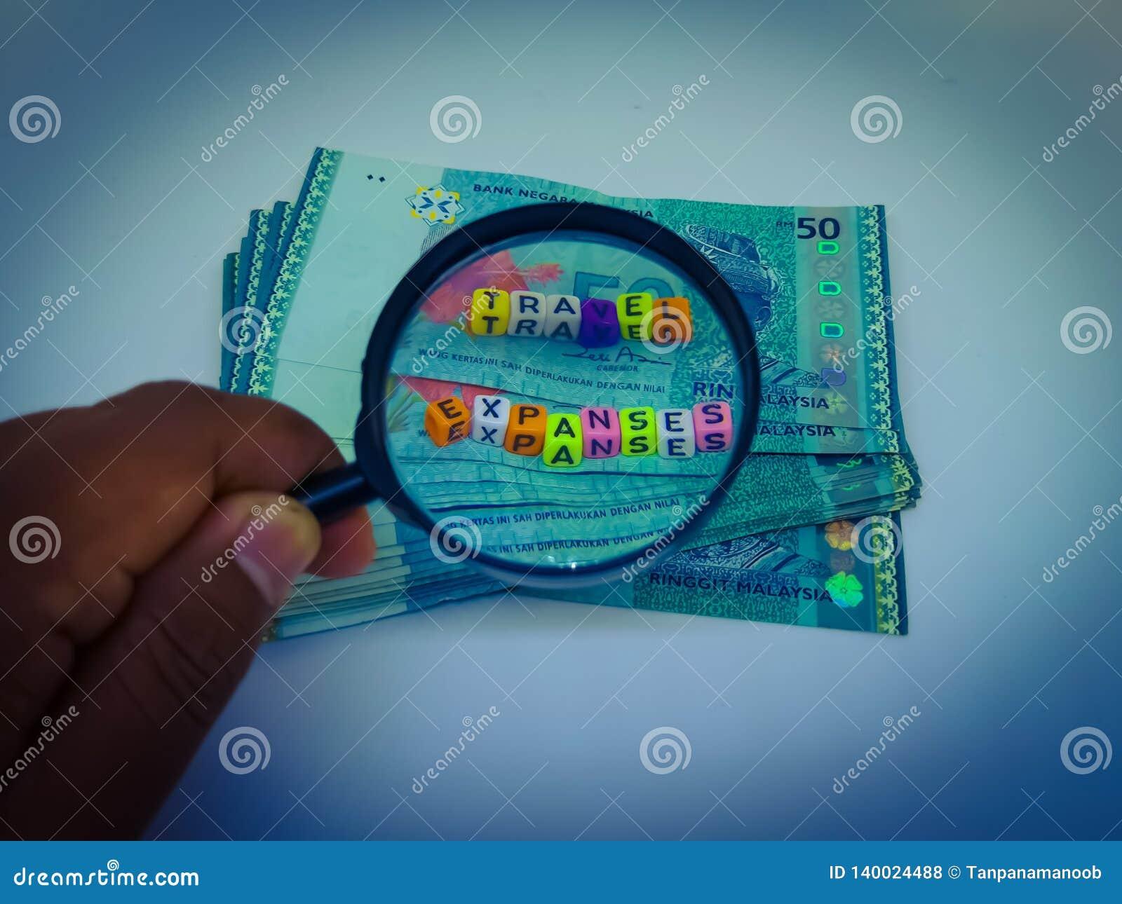 Ein Block von BuchstabeReisekosten, Währung, Lupe mit einem weißen Hintergrund