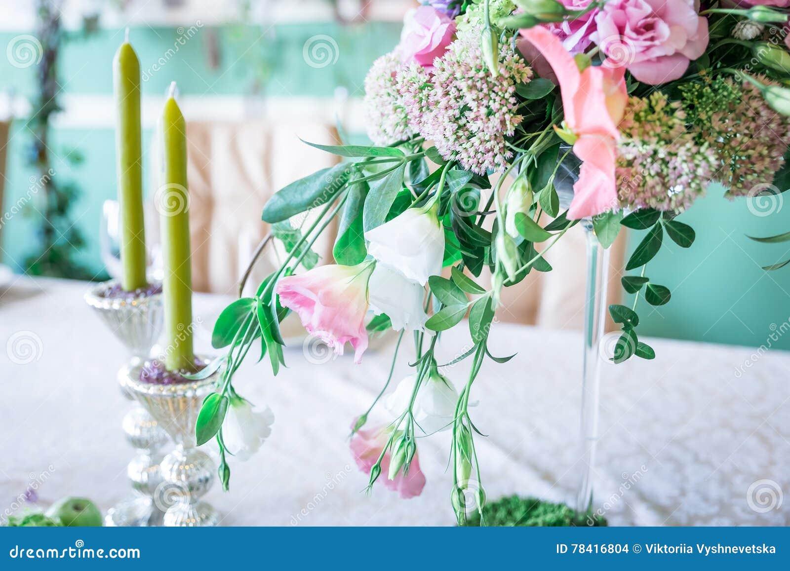 Ein Blumenstrauß Von Blumen Auf Einem Stand Mit Kerzen Und Dekor Für
