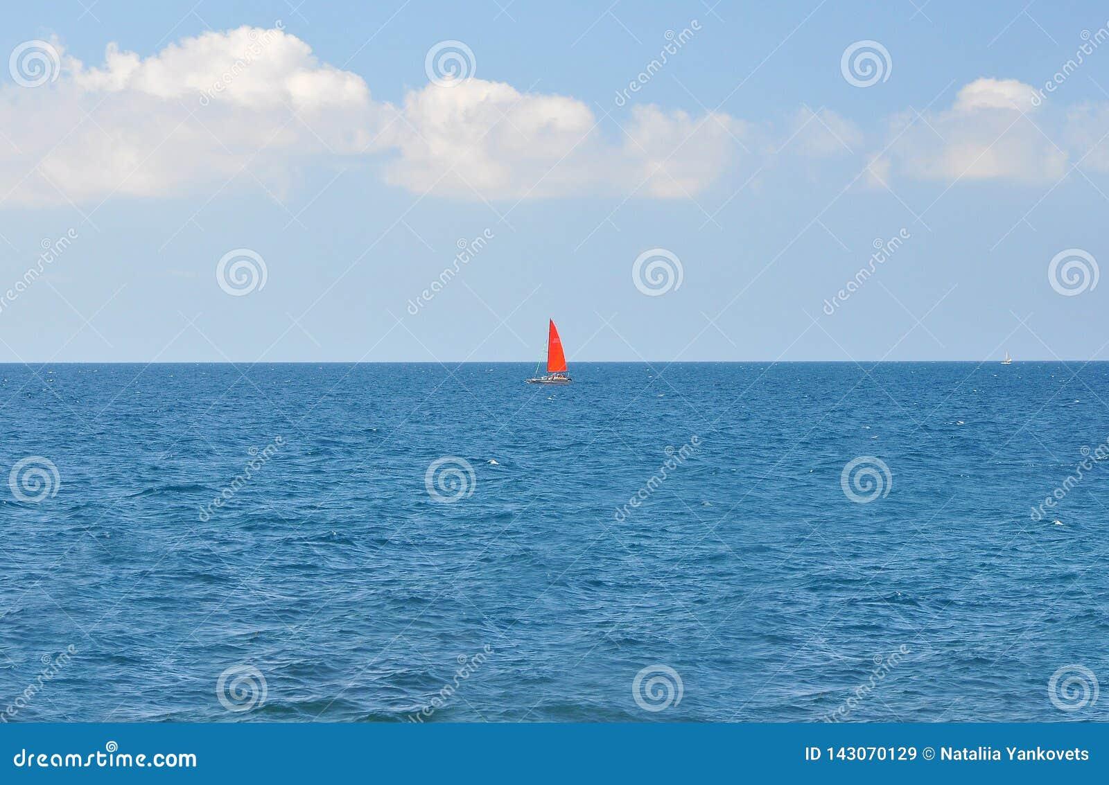 Ein Boot mit einem roten Segel, das entlang das blaue Meer auf einem Hintergrund des blauen Himmels schwimmt