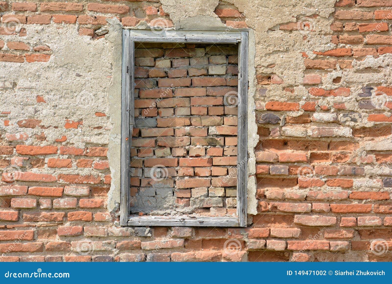 Ein bricked Fenster mit Holzrahmen auf der Wand des roten Backsteins