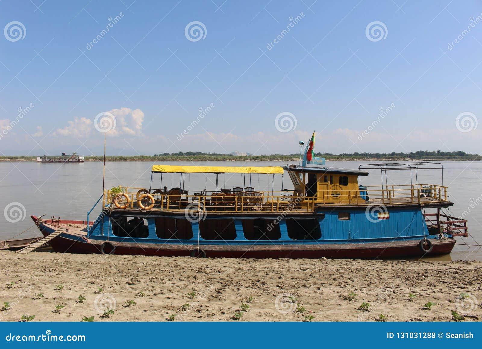 Ein Delphin aufpassendes tourboat auf dem Irrawaddy