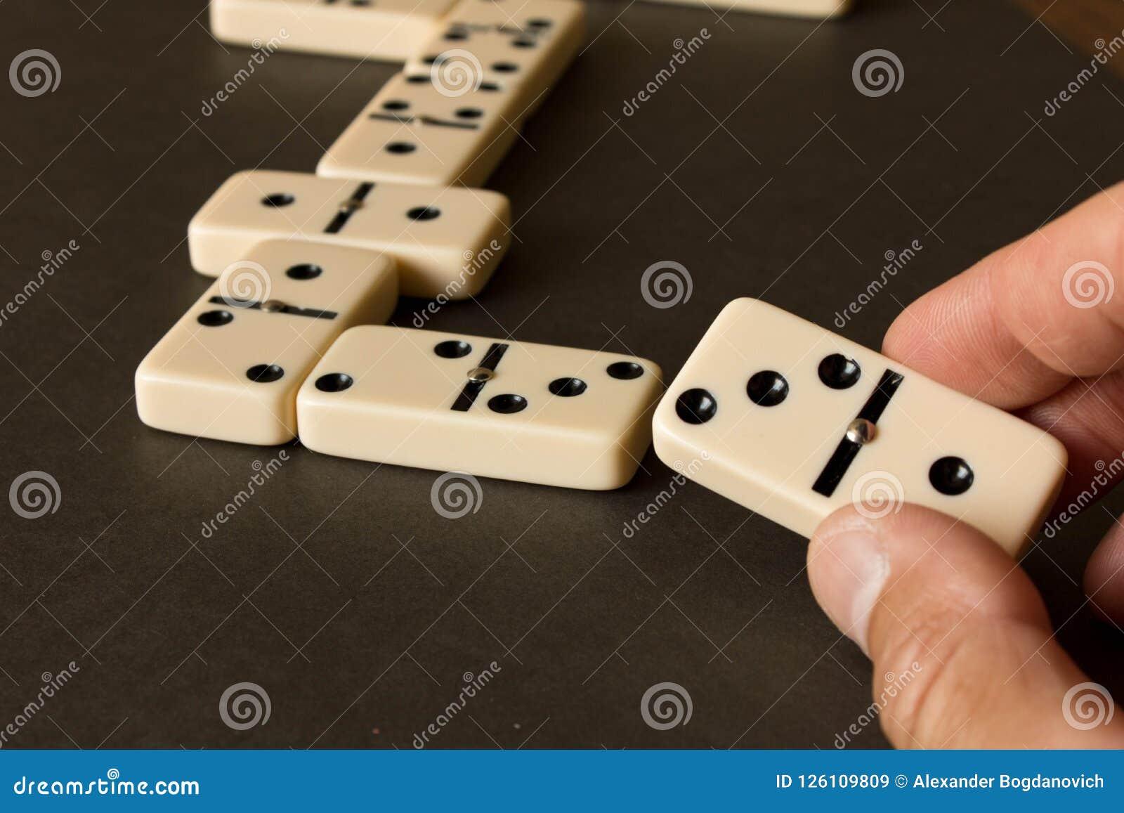 Ein Dominospiel auf einer dunklen Tabelle Das Konzept des Dominospiels Mann ` s Hand mit einem Domino Abschluss oben