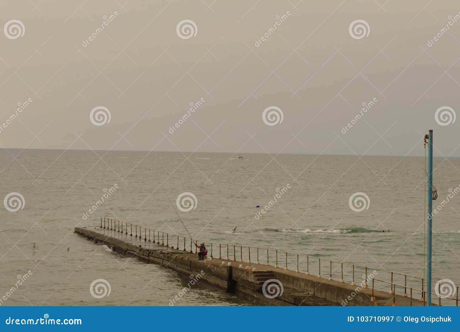 Ein einziger Fischer, der auf dem Pier sitzt