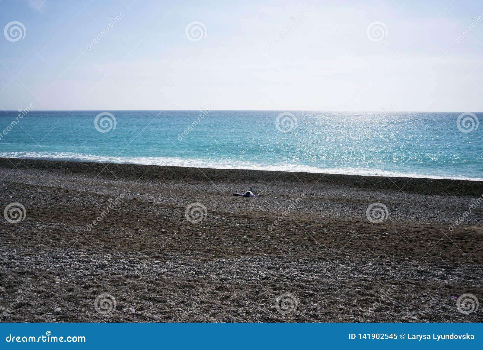 Ein einziger Mann auf einem verlassenen Pebble Beach auf dem Cote d Azur Erholung durch das Meer