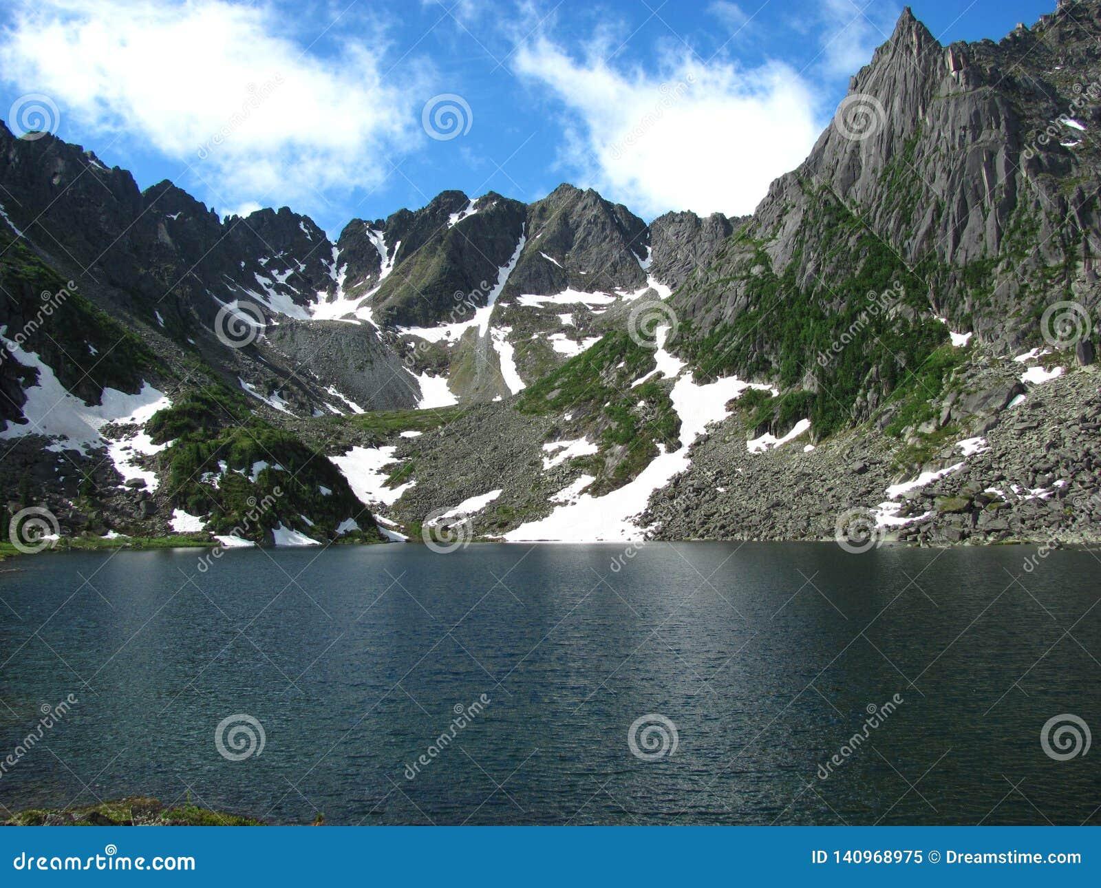 Ein enormer See umgeben durch schneebedeckte Spitzen