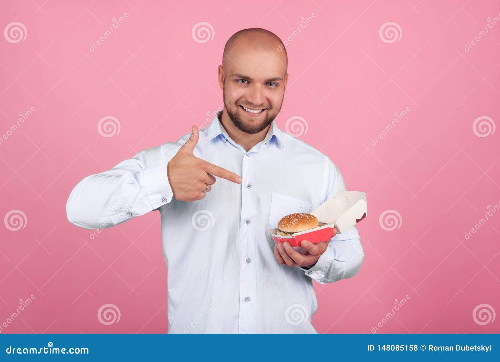 Ein erfüllter Mann mit einem üppigen Bart und ein Kahlkopf Punkte sein Finger zum Burger, den er in seinen Händen und in Blicken