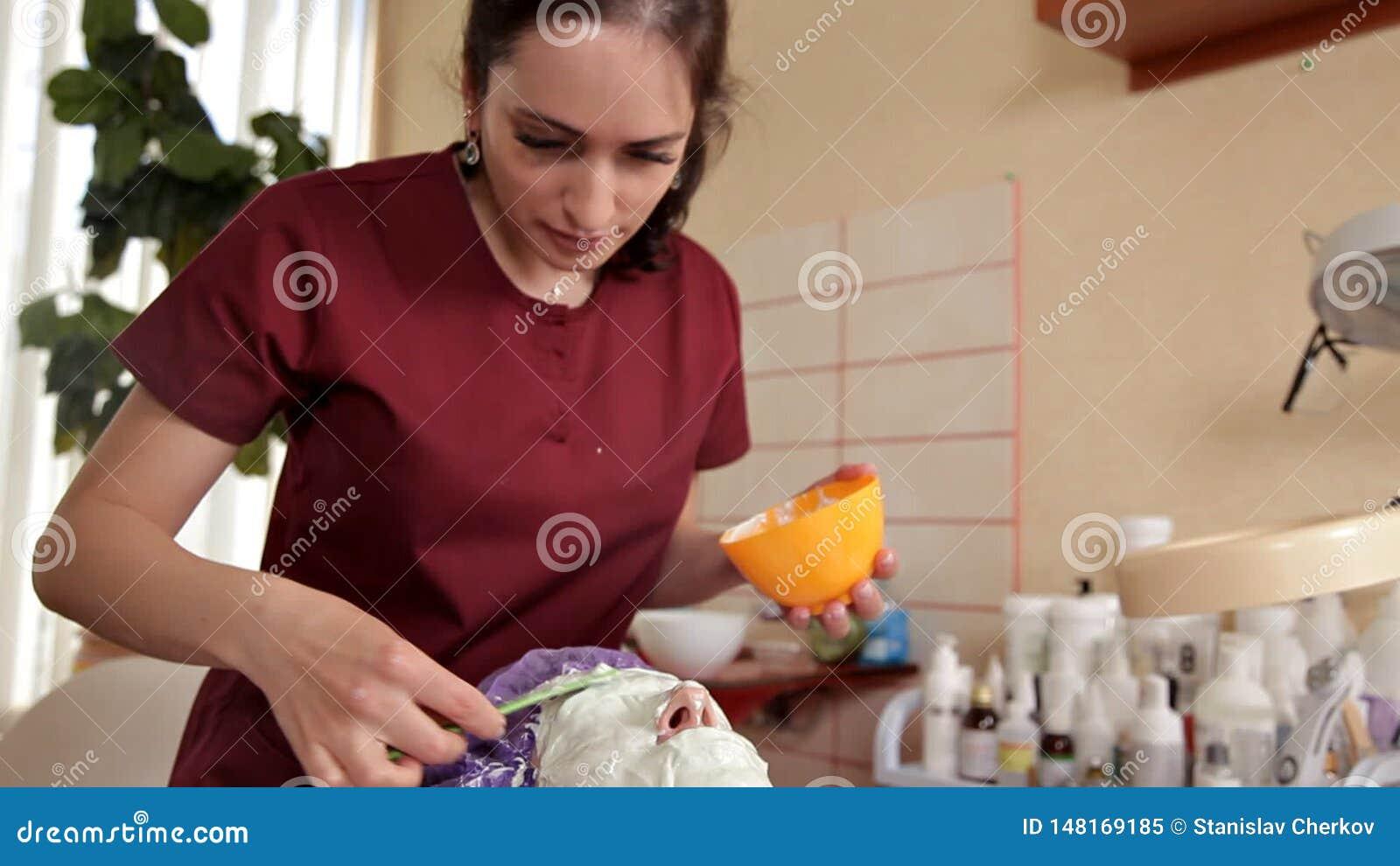 Ein erfahrener Cosmetologist bereitet eine gesunde Maske f?r den Kunden vor Sie steht auf und ber?hrt das Gesicht mit einer B?rst stock video