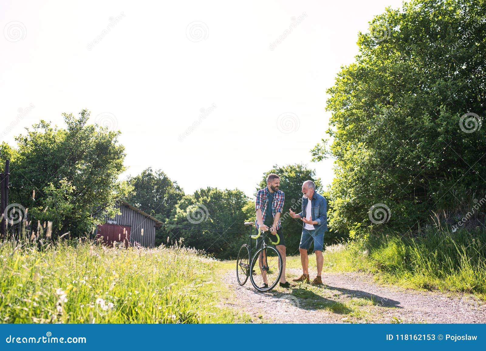 Ein erwachsener Hippie-Sohn mit dem Fahrrad und älterem Vater, die in sonnige Natur gehen