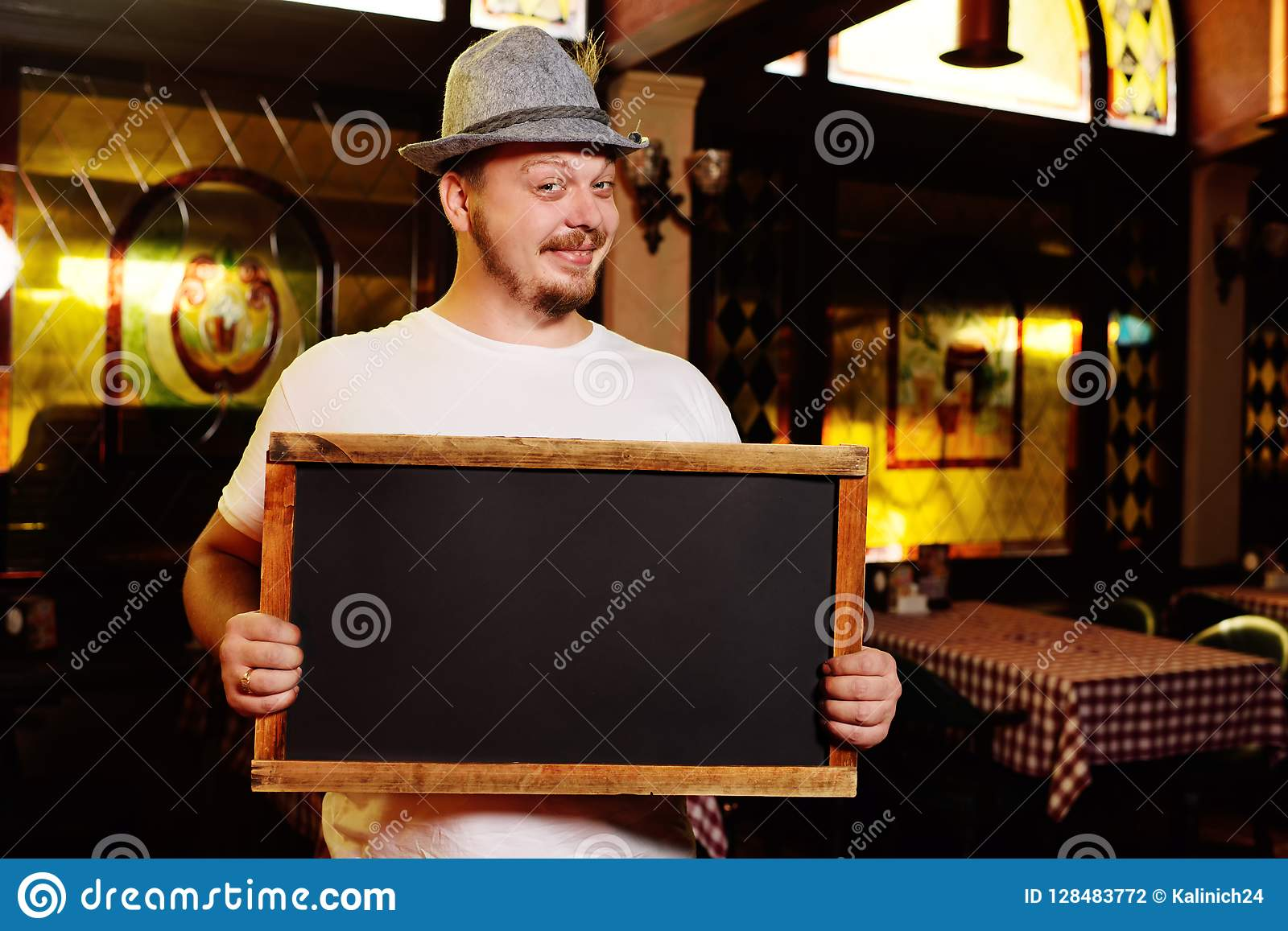 Ein fetter netter Mann in einem bayerischen Hut mit einer Feder während der Feier von Oktoberfest hält ein Zeichen oder eine Tafe