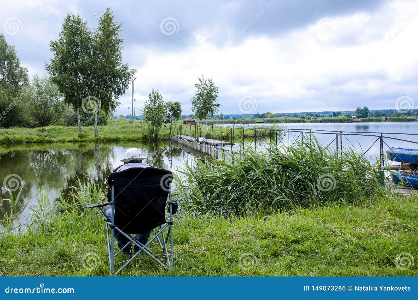 Ein Fischer in einer Kappe sitzt in einem Stuhl nahe dem See mit einer Angelrute und fängt Fische