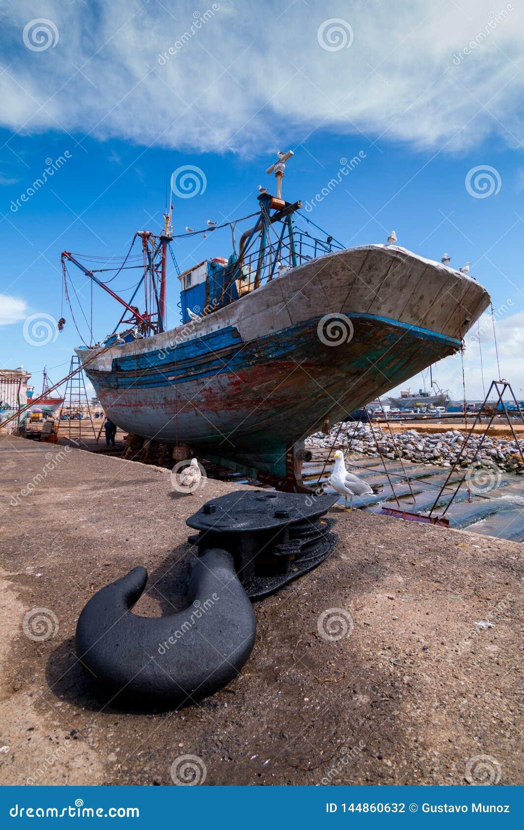 Ein Fischerboot angekoppelt an den Dockwartung eine volle Reparatur mit einem Bootshaken im Vordergrund