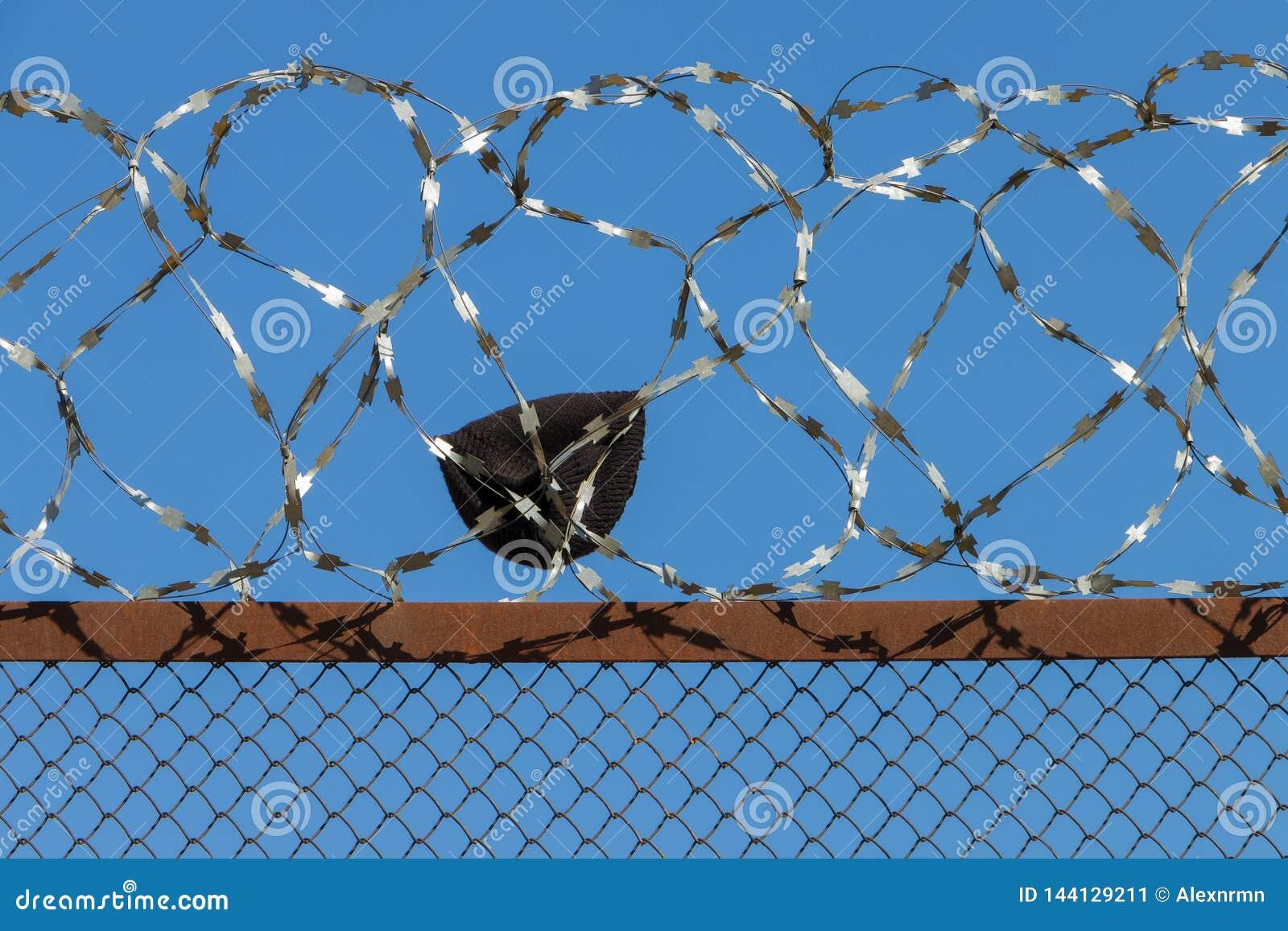 Ein Fragment von Kleidung auf dem Zaun mit Stacheldraht