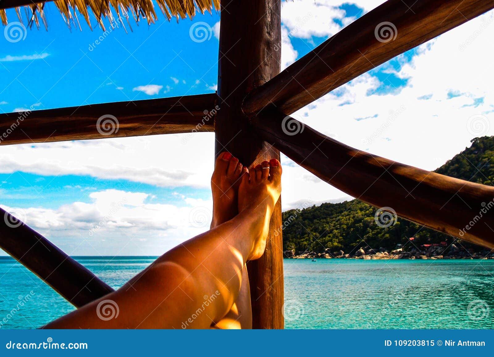 Ein Frau ` s stellen Füße auf einem Balkon das Meer auf einer Tropeninsel gegenüber
