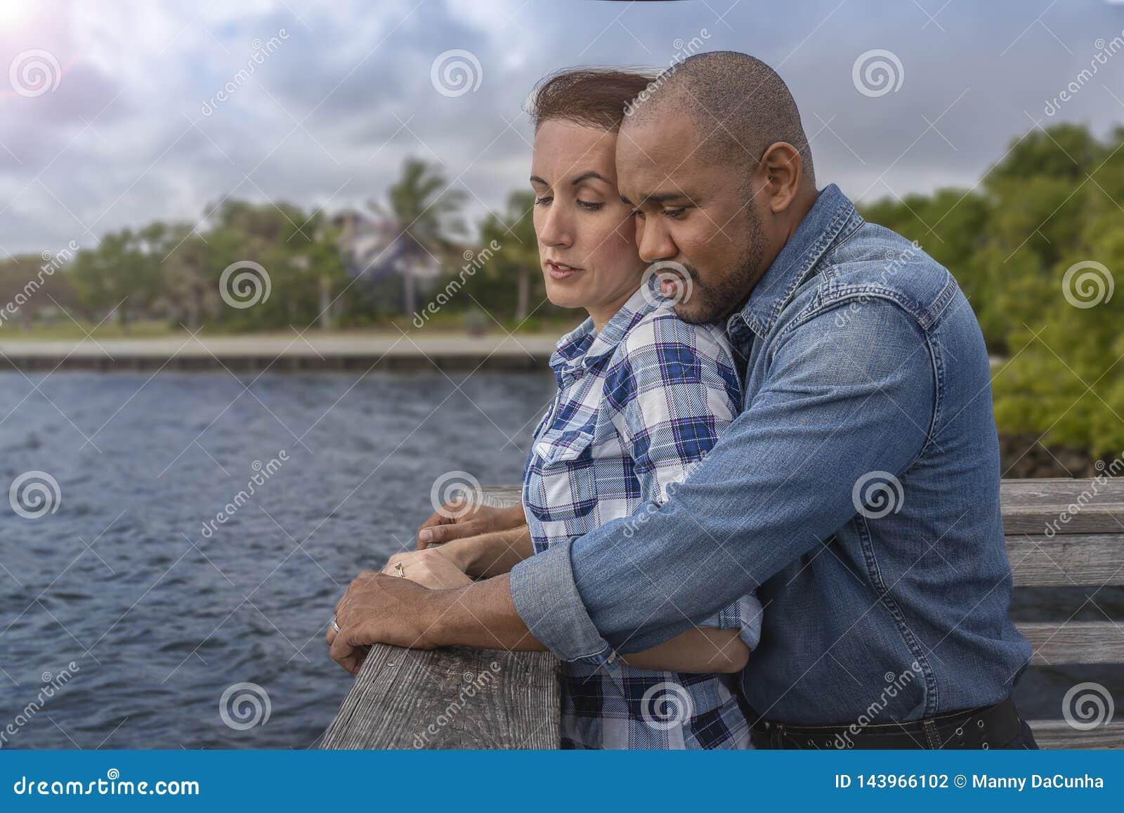 Ein gemischtrassiges Paar schaut über dem Pier