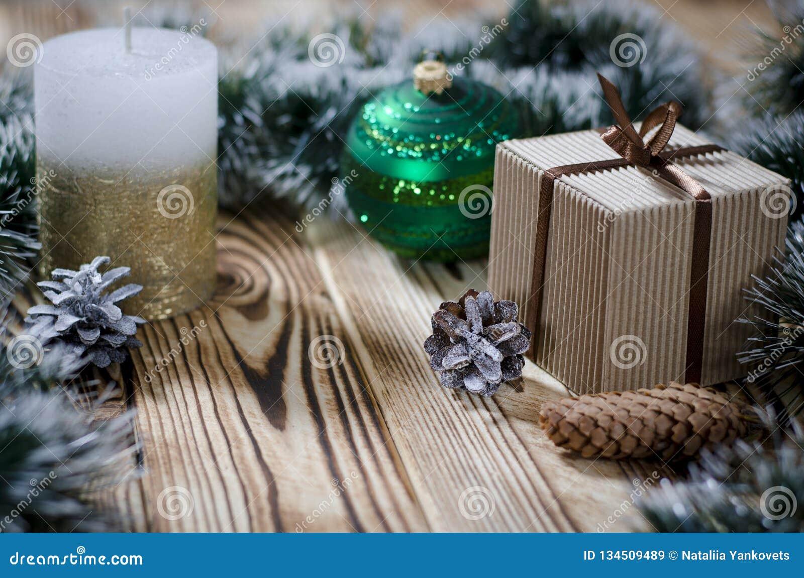 Ein Geschenk legt auf einen Holztisch nahe bei einer Kerze, Kegeln und einem Engel vor dem hintergrund der Weihnachtsdekorationen