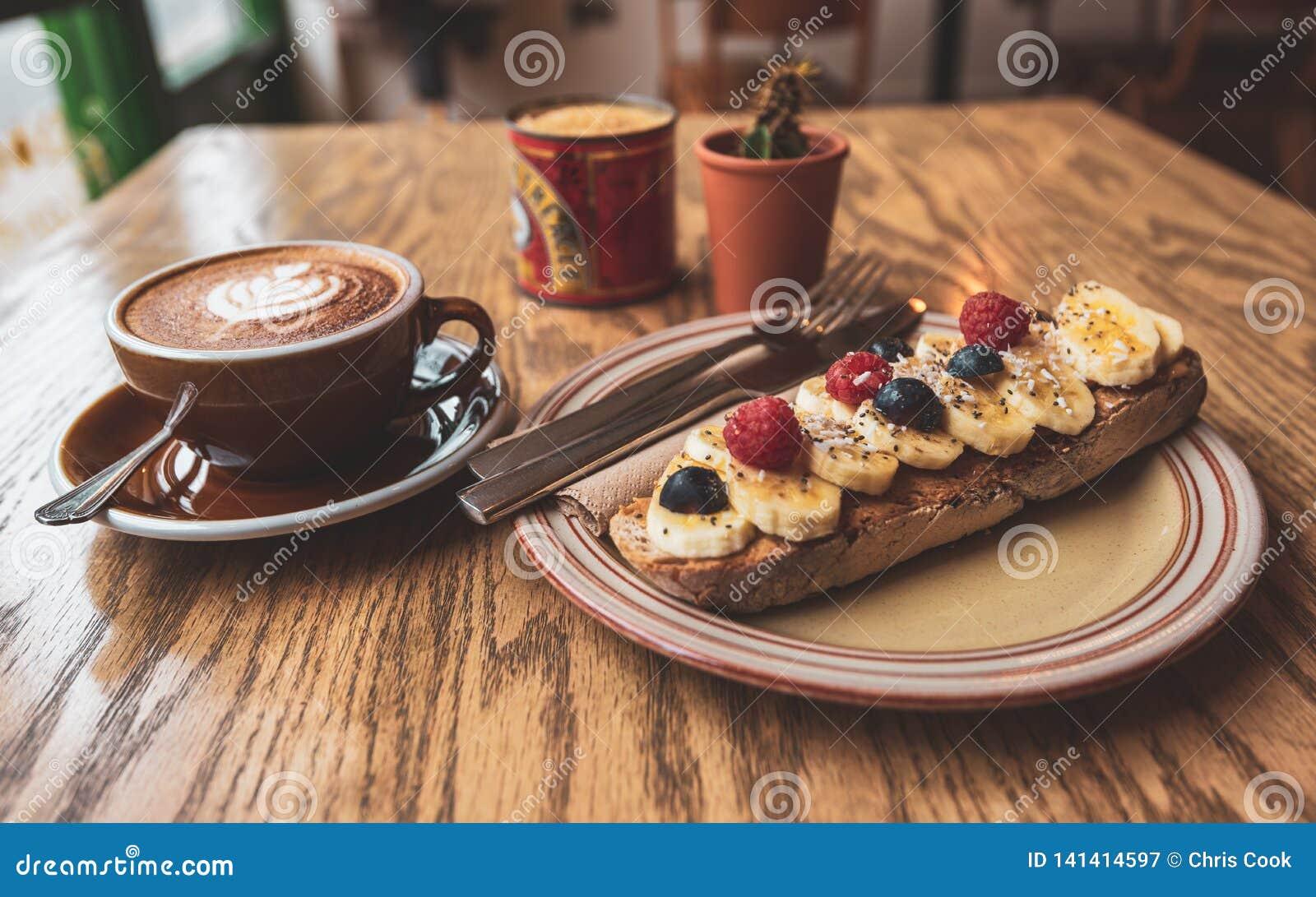 Ein gesundes Morgenfrühstück des Kaffee- und Bananentoasts auf Sauerteig