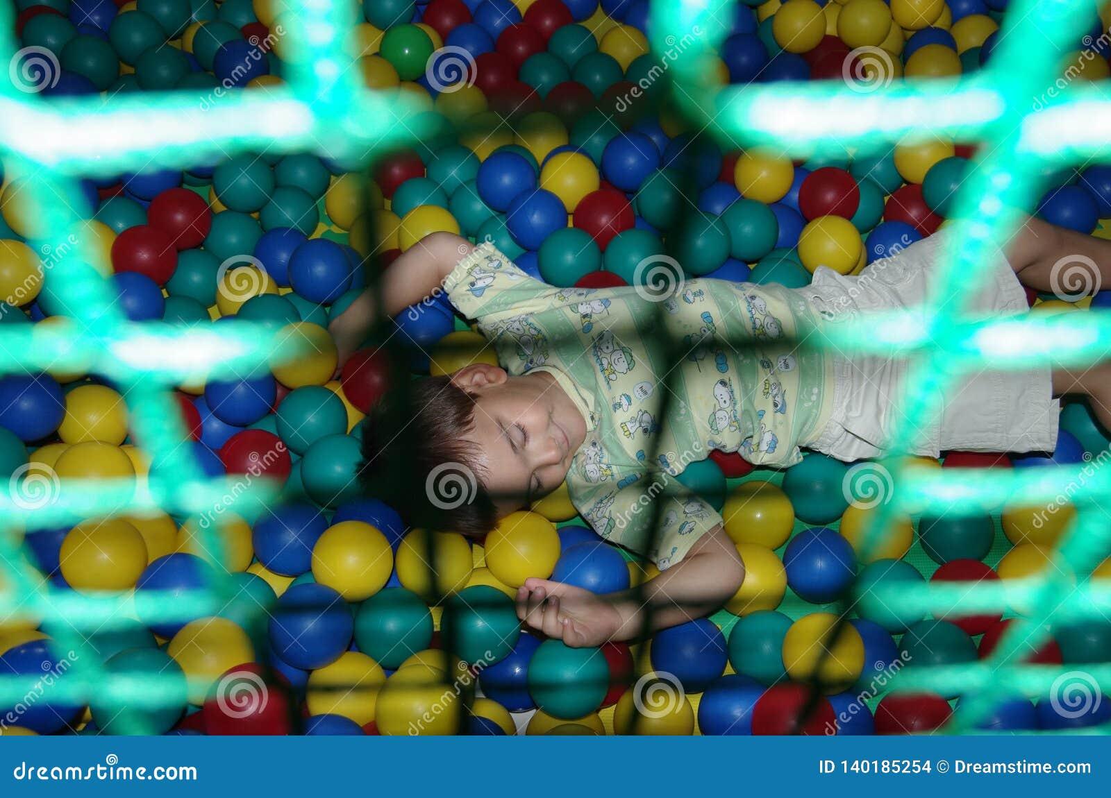 Ein glückliches Baby liegt auf Plastikbällen
