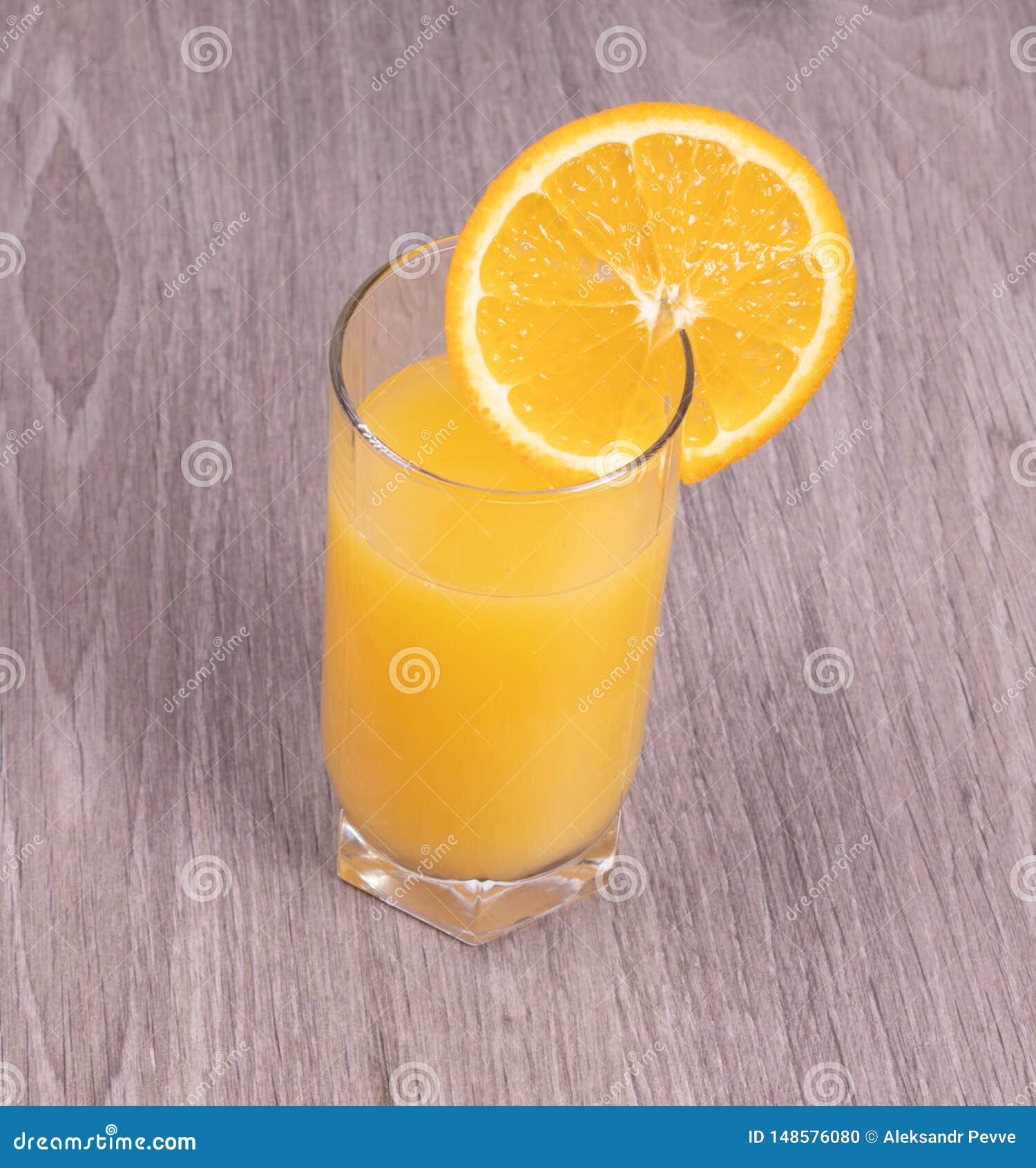 Ein Glas Orangensaft mit einer Scheibe der Orange auf einem h?lzernen strukturierten Hintergrund