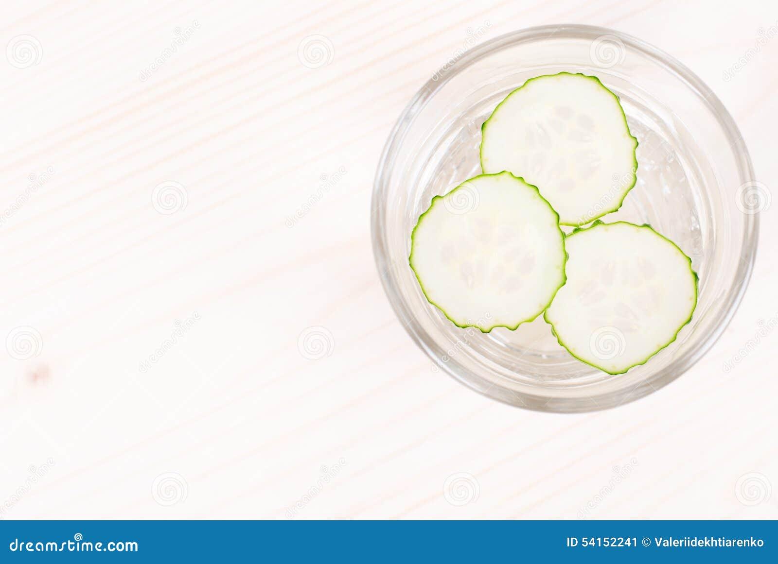 ein glas wasser mit drei scheiben frischer gurke auf einem. Black Bedroom Furniture Sets. Home Design Ideas