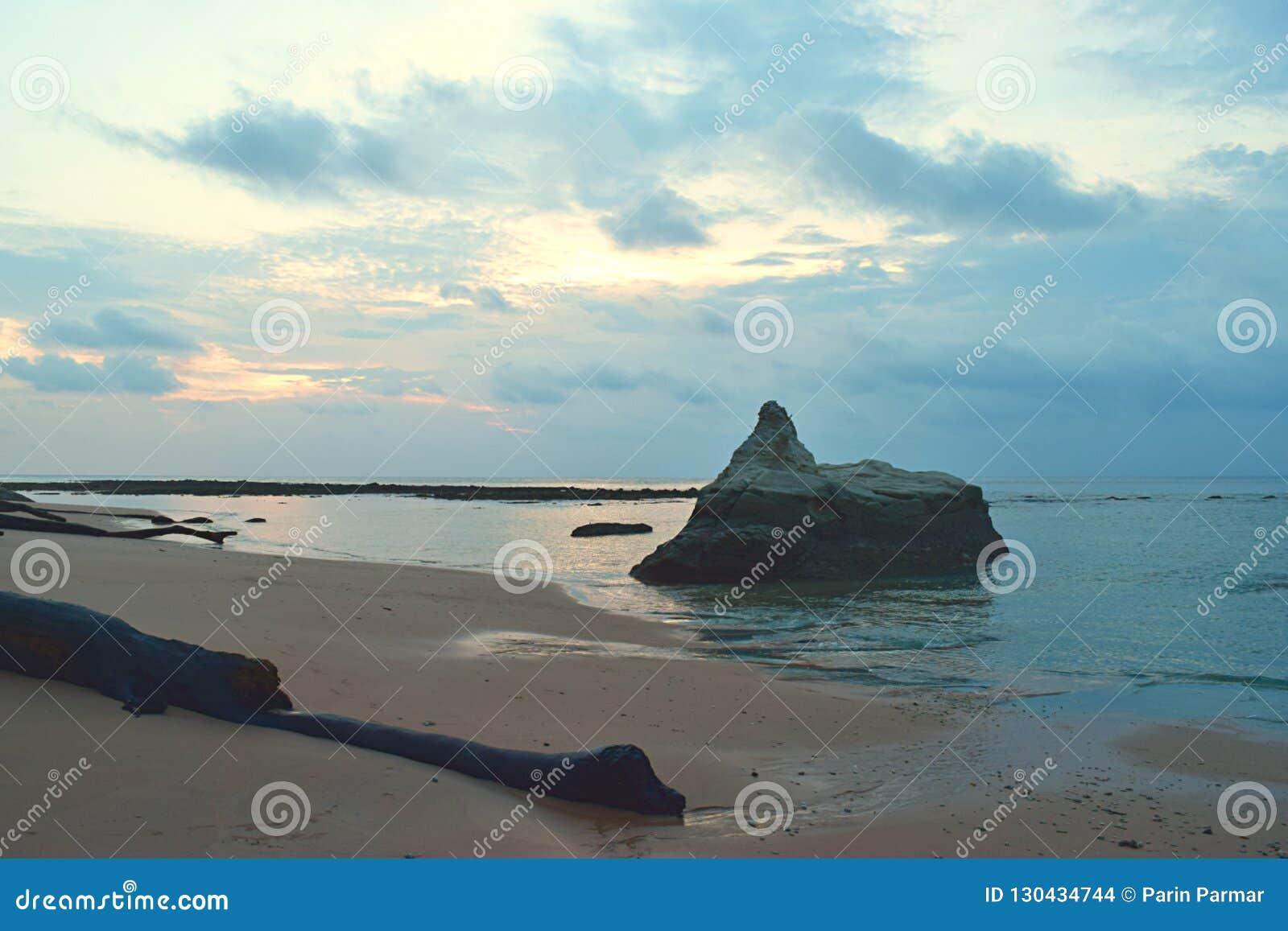 Ein großer Stein im Wasser des ruhigen Sees bei ursprünglichem Sandy Beach mit Farben im Morgen-bewölkten Himmel - Sitapur, Neil