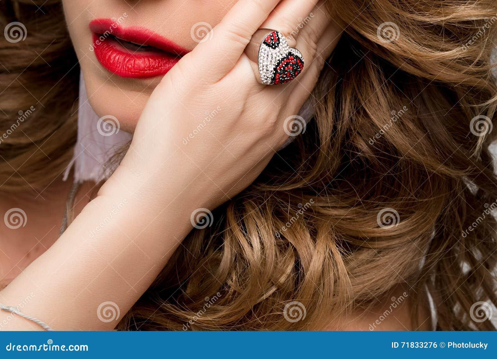 Ein großes Porträt der Lippen und der Hand einer Frau mit dem Ring Ring mit Edelsteinen, Silber und Rot Gesicht, rote Lippen