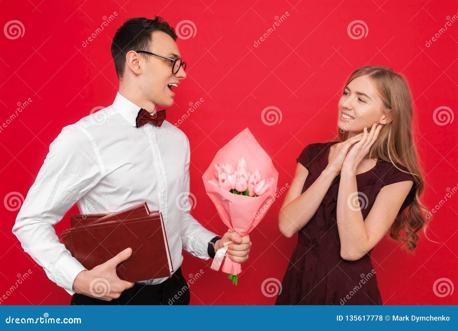 Ein hübscher Student, tragende Gläser, gibt seiner Freundin ein Geschenk und einen Blumenstrauß von Blumen gegen einen roten Hint