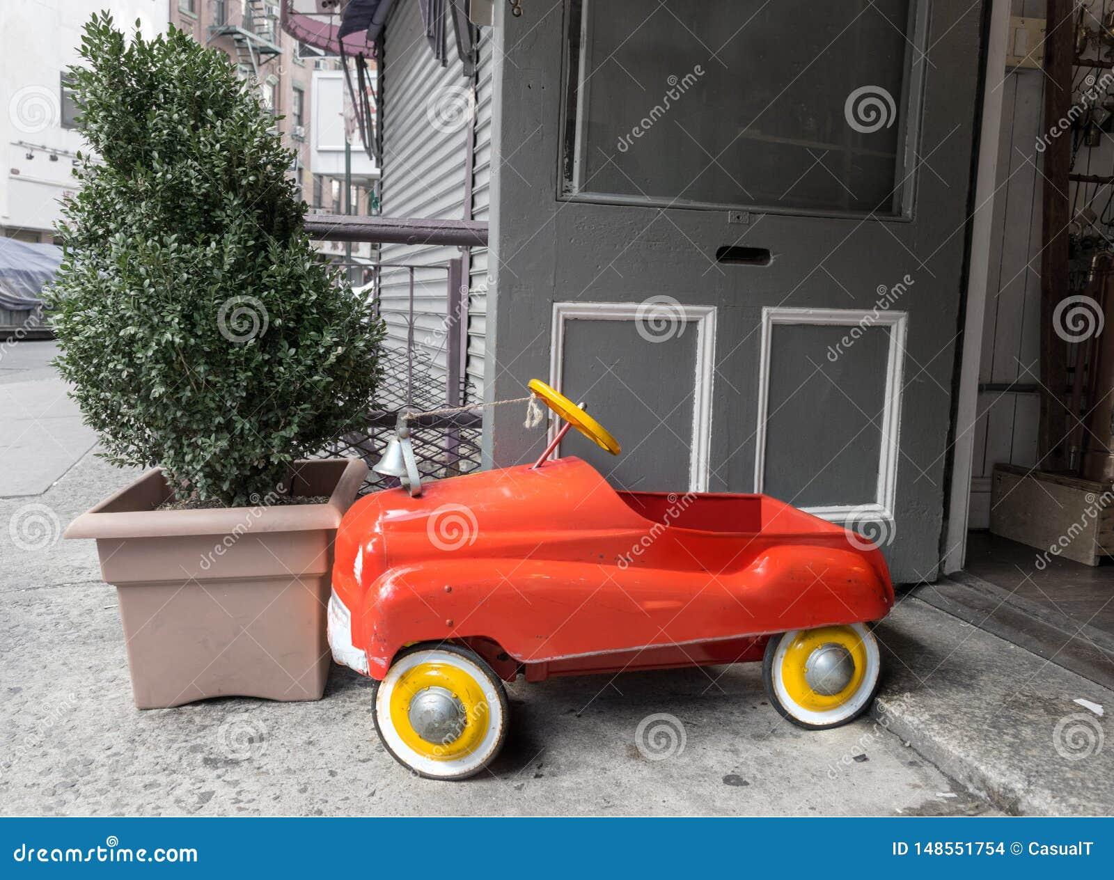 Ein helles rotes u. gelbes Spielzeugl?schfahrzeug steht heraus againsta trostlose graue konkrete Umwelt