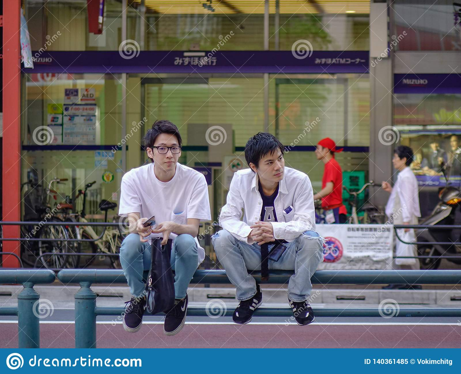 Ein homosexuelles Paar, das auf Straße von Tokyo sitzt