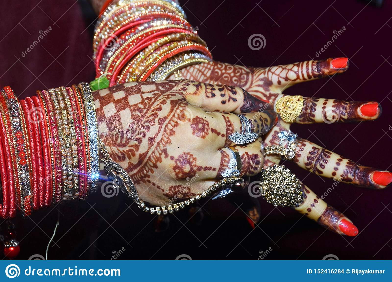 Ein indischer Bräutigam, der ihren goldenen Ring in ihrem schönen Schuss des Fingers zeigt