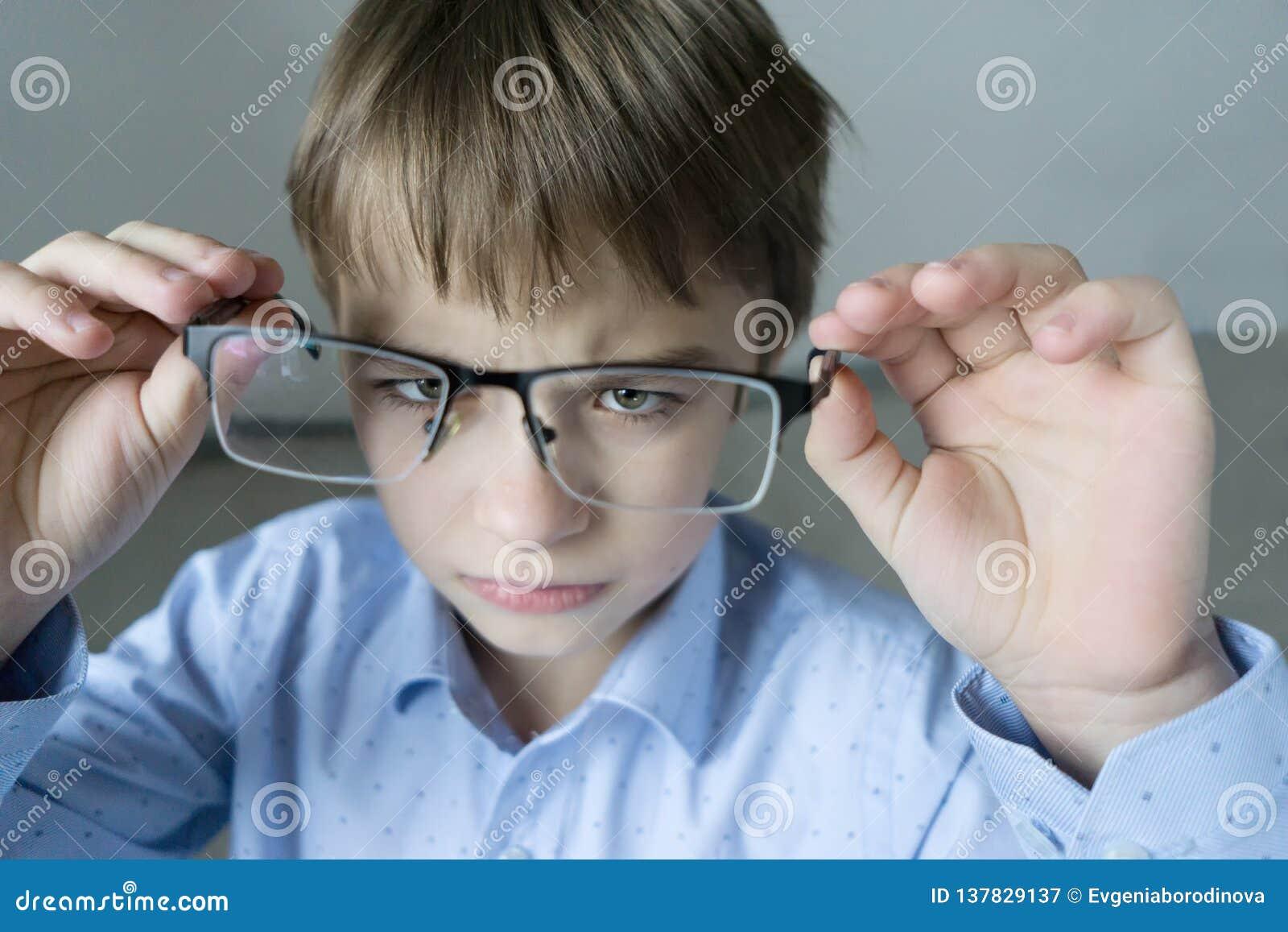 Ein 9-jähriger Junge in einem blauen Hemd mit Gläsern überprüft sein Sehvermögen Unzufrieden gemacht mit der Tatsache, die Gläser