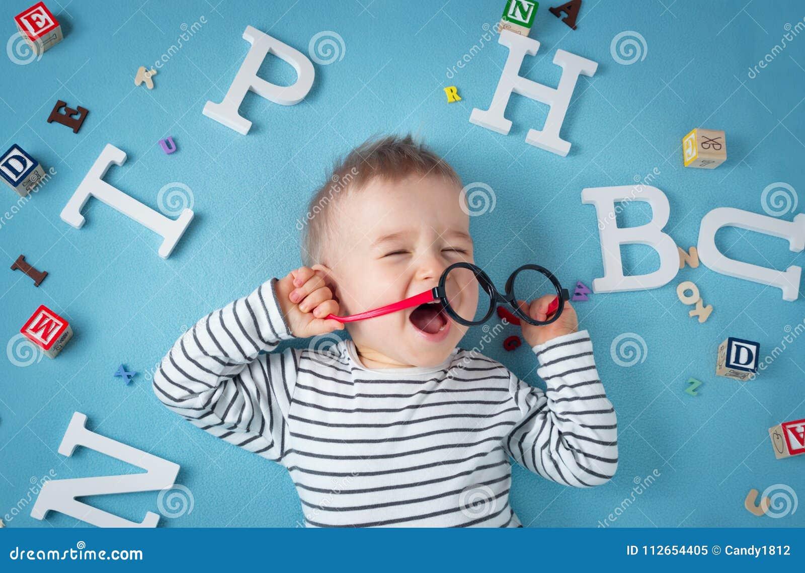 Ein jähriges Kind, das mit Schauspielen und Buchstaben liegt