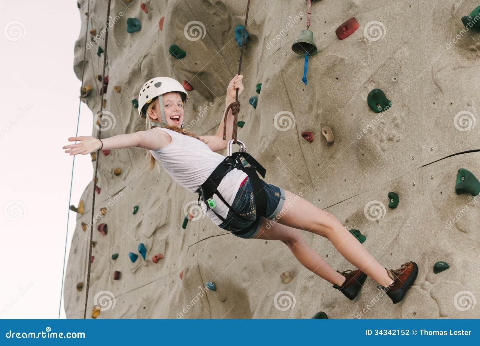 Ein jugendlich Mädchen, das auf einer Felsenwand zurück sich lehnt an der Überrollschutzvorrichtung klettert